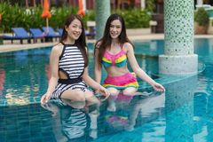 Two young women friends enjoy in swimming pool. Two young women friends enjoy in the swimming pool stock photography
