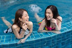 Two young women friends enjoy in swimming pool Royalty Free Stock Photography