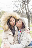 Two young women friends kissing each other for fun. Two women friends kissing each other for fun stock photography