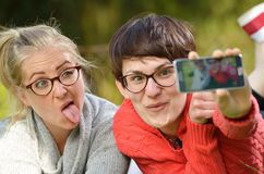 Two young women - friends are making themselves a photo. Royalty Free Stock Images