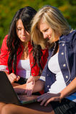 Two young women friends outdoors with a laptop Royalty Free Stock Images