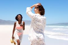 Two young women friends playing on the beach Royalty Free Stock Images