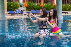 Two young woman friends splashing water in swimming pool Stock Photo