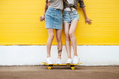 Two young women friends standing over yellow wall. Cropped image of two young women friends standing over yellow wall Royalty Free Stock Images