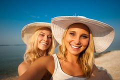 Two young women friends taking selfie on beach.  royalty free stock photos