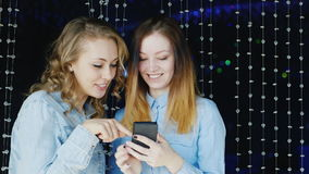 Two young women friends use your smartphone in a nightclub. HD video stock video footage