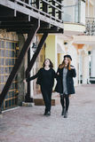 Two young women friends walking on a street. Two young beautiful women friends walking on a street Royalty Free Stock Images
