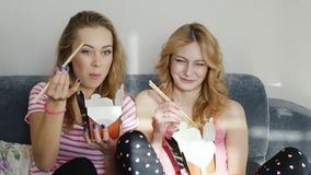 Two young women friends watch together a funny movie. Eat food from wooden chopsticks paper bags. HD video stock video