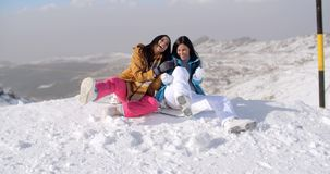 Two young women frolicking in the snow. As they sit on a mountain summit at the edge of a ski run laughing merrily stock footage