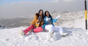 Two young women frolicking in the snow. As they sit on a mountain summit at the edge of a ski run laughing merrily Royalty Free Stock Image