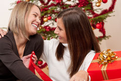Two young women in front of Christmas tree Royalty Free Stock Image