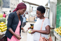 Two young women at fruit market. Stock Photos