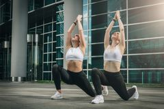 Two young women, girls doing stretching exercises, warm up, doing yoga on city street. Workout, couching on city street. royalty free stock photo