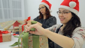 Two young women in glasses and red caps tie bows on gifts and laugh. stock video