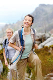 Two young women go on an adventure. Friends hiking together outdoors exploring the wilderness and having fun stock photo