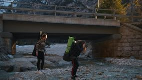 Two young women go on a rocky river with the backpacks and guitar under a bridge in the mountains stock footage