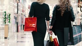 Two young women go shopping with their purchases. View from behind stock video