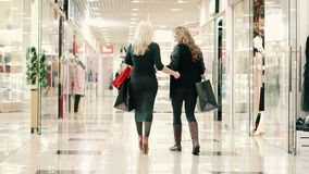 Two young women go shopping with their purchases. View from behind stock footage
