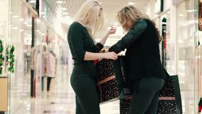 Two young women go shopping with their purchases. View from behind stock video footage