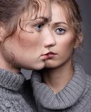 Two young women in gray sweaters on grey background. Beautiful g Stock Images