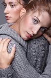Two young women in gray sweaters on grey background. Beautiful g Stock Photography
