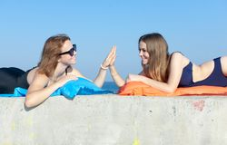 Two young women greeting high five gesture each other. Two girls in swimwear lying on concrete wall and making hi-five gesture looking each on other Royalty Free Stock Images