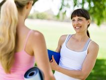 Two young women with a gym mat chatting in the park. Two young women standing and chatting with a blue gym mat in the park royalty free stock photo