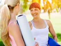 Two young women with a gym mat chatting in the park. Two young women standing and chatting with a blue gym mat in the park royalty free stock images