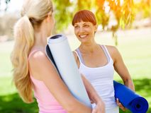 Two young women with a gym mat chatting in the park. Two young women standing and chatting with a blue gym mat in the park stock image