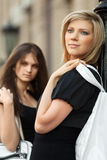 Two young fashion women with handbag on city street Royalty Free Stock Photo