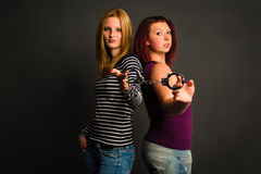 Two young women with handcuffs Royalty Free Stock Images