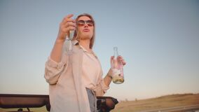 Two young women have fun in a cabriolet during a road trip at sunset. They drink wine and sing songs. Young travelers