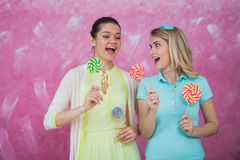 Two young women have fun with lollipops, celebrating party conce. Pt.  Pink background, happiness and joy Stock Image