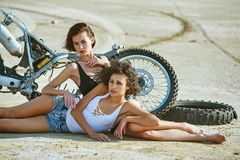 Two young women have fun playing on a disassembled motorcycle Royalty Free Stock Photos