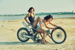 Two young women have fun playing on a disassembled motorcycle Royalty Free Stock Images