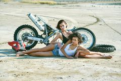 Two young women have fun playing on a disassembled motorcycle royalty free stock photography