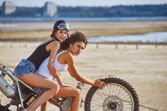 Two young women have fun playing on a disassembled motorcycle royalty free stock image
