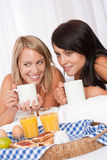 Two young women having breakfast in white bed Royalty Free Stock Photos