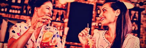 Two young women having cocktail drinks Stock Photos