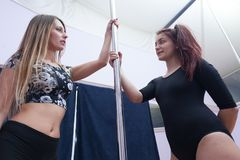 Two women at pole dance lesson. Two young women having a conversation during a pole dance lesson Stock Image