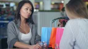 Two young women having discussing something sitting in cafe in mall. Close up. Professional shot in 4K resolution. 103. You can use it e.g. in your commercial stock video footage