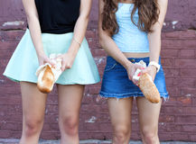 Two young women having fun with bread Royalty Free Stock Photos