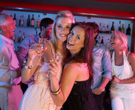 Two Young Women Having Fun In Busy Bar. Two Young Women Having Fun Smiling In Busy Bar stock photos