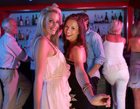 Two Young Women Having Fun In Busy Bar Stock Photos