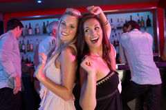 Two Young Women Having Fun In Busy Bar Royalty Free Stock Images