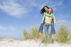 Two young women having fun in dunes Stock Images