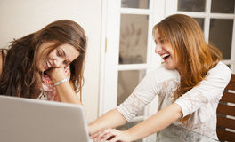 Two young women having fun in front of laptop Royalty Free Stock Photo