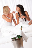 Two young women having fun in luxury hotel room Royalty Free Stock Image