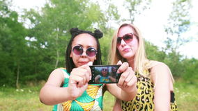 Two young women having a great time taking selfies. Close up of two beautiful young women having fun while taking selfies of themselves using a mobile phone stock video footage