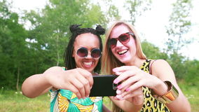 Two young women having a great time taking selfies. Close up of two beautiful young women having fun while taking selfies of themselves using a mobile phone stock video